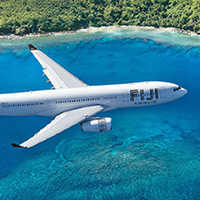 Fiji Airways plane flying over turquoise waters